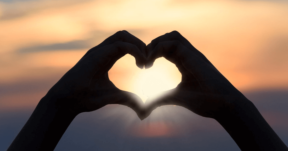 Two hands forming a love heart shape with a sunset in the distance